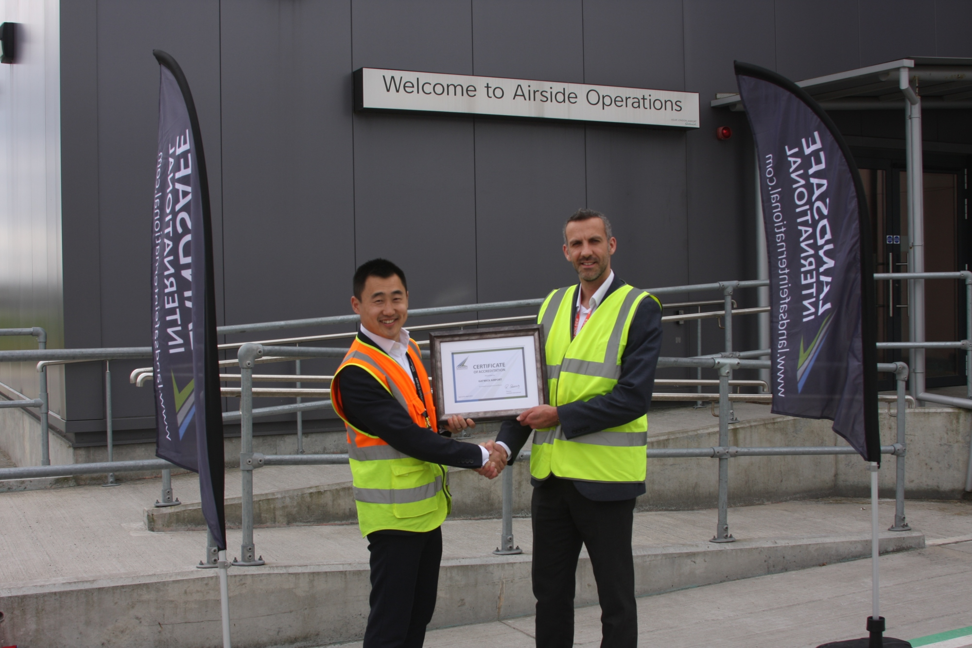 Kan Ni (Gatwick Head of Airside) and Richard Stuttard (Landsafe International) with Gatwick's accreditation award